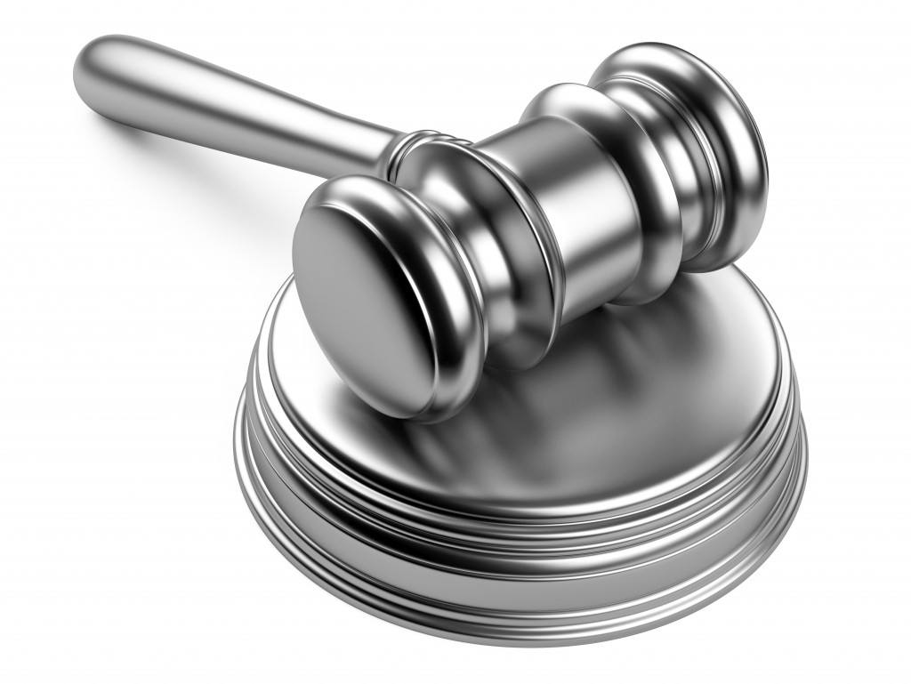A silver gavel resting on a silver striking plate. Trust and estate planning.